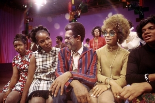 A colorfully clad Ellis Haizlip is flanked by four female guests on the set of Mr. SOUL!