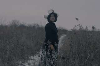 Screen shot from The Wandering shows a woman standing alone on a dirt road that leads through a field