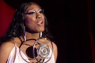 "Bambi Banks Couleé, shown singing into a vintage microphone, plays The Performer in ""The Wandering."""